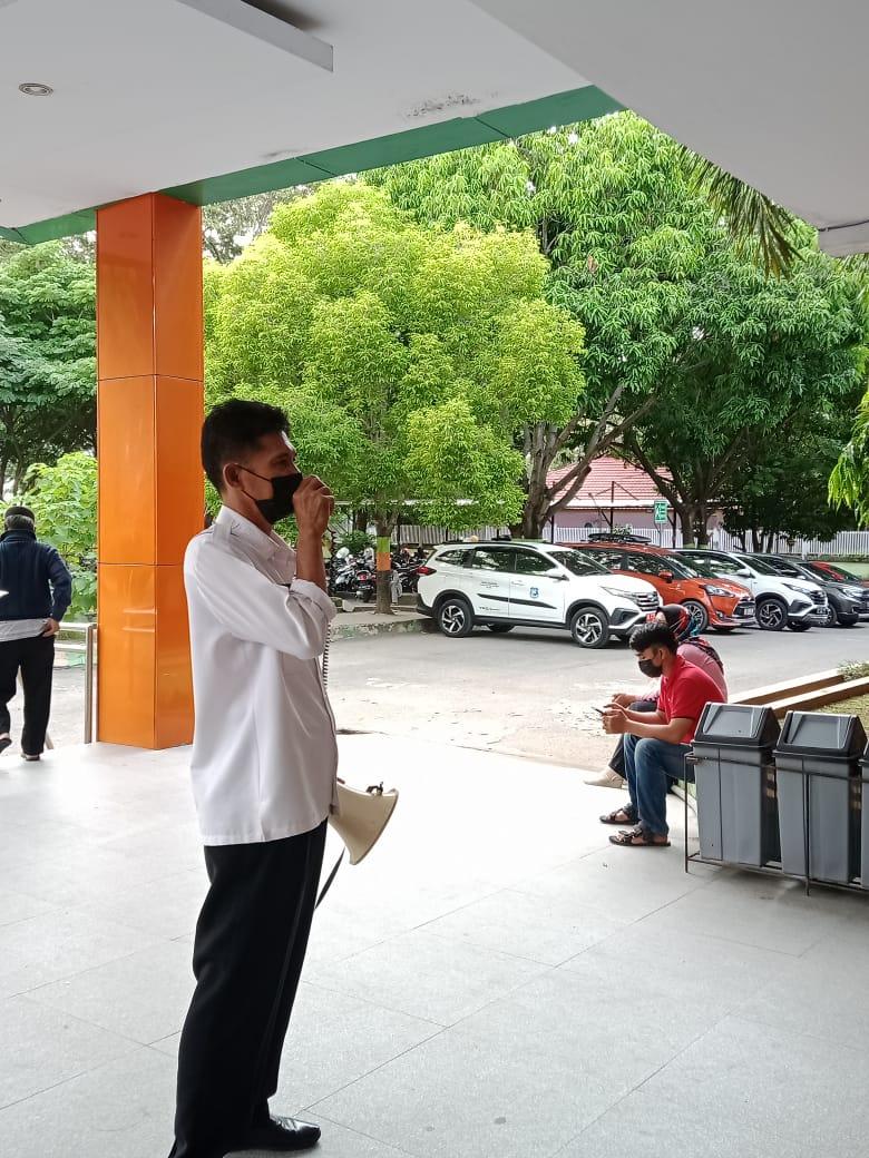 seorang securty rsud Bulukumba menghimbau pengunjung memakai masker dan menjaga jarak.